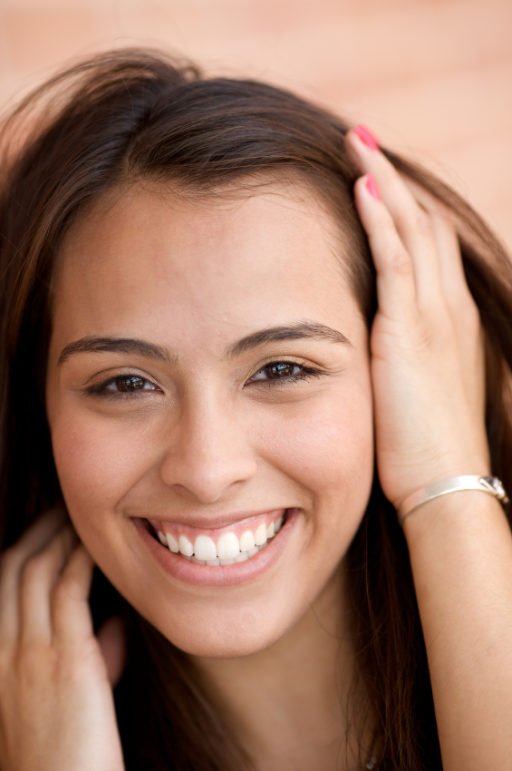 Hispanic woman smiling with hand in hair at Water's Edge Dental in Boise, ID